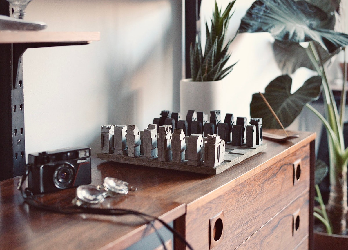 A custom concrete chess set sits on a cabinet next to a camera and glasses, and would be a perfect gift for a fan of Netflix's 'The Queen's Gambit.'