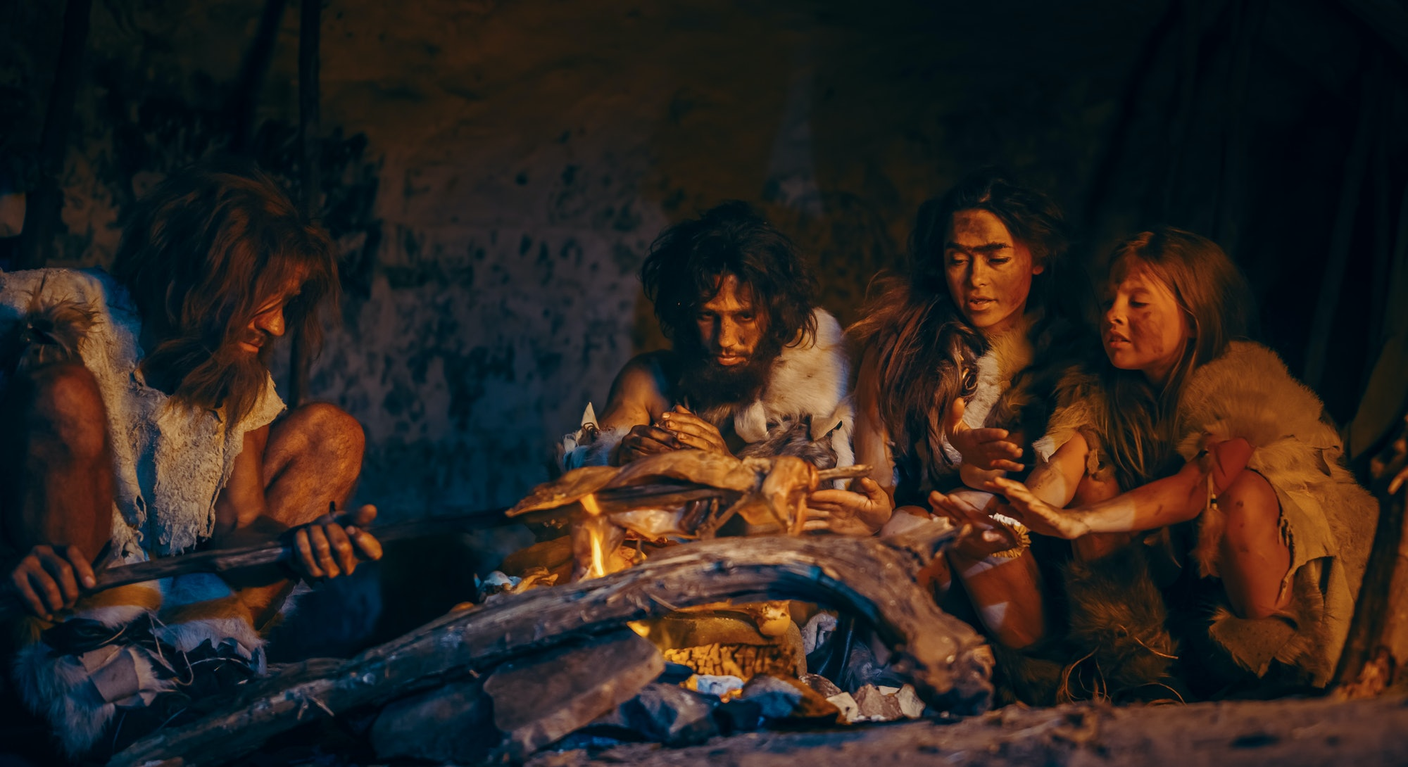 Neanderthal or Homo Sapiens Family Cooking Animal Meat over Bonfire and then Eating it. Tribe of Prehistoric Hunter-Gatherers Wearing Animal Skins Grilling and Eating Meat in Cave at Night