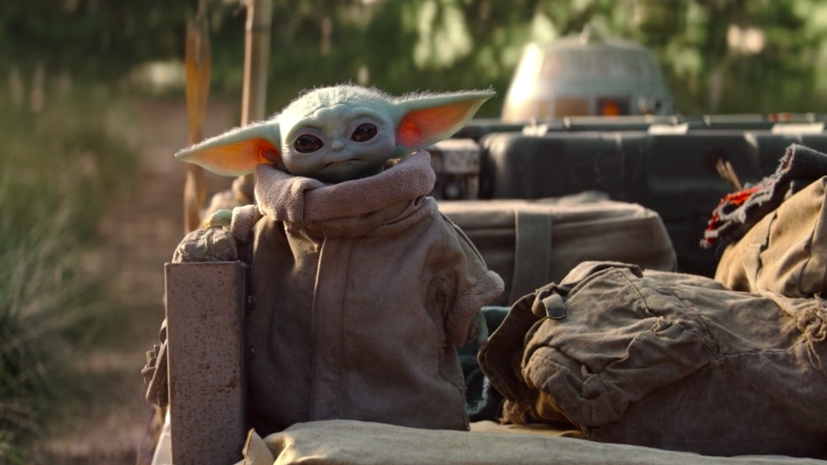 Baby Yoda stands on the bed of a speed racer, staring cutely onto the screen.