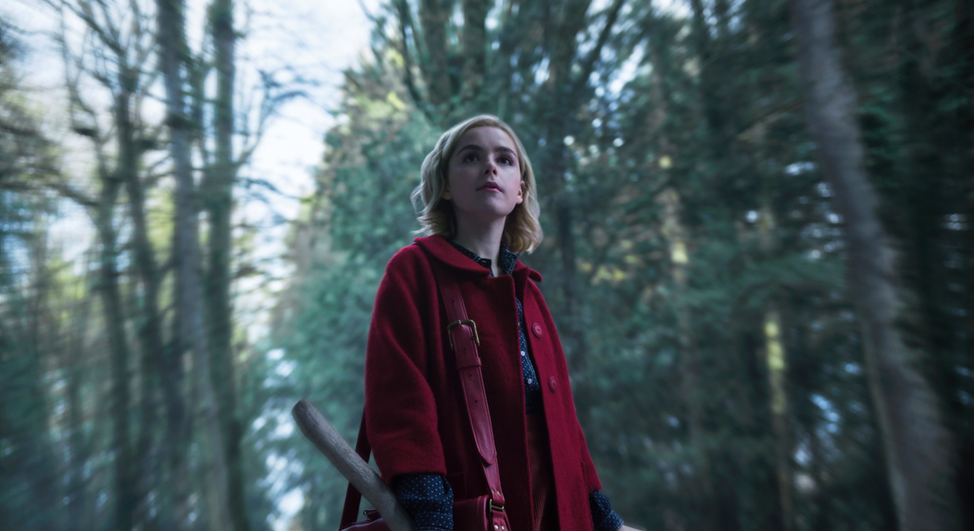 A still of Kiernan Shipka, from Chilling Adventures of Sabrina, standing in a wooded area, wearing a red cape