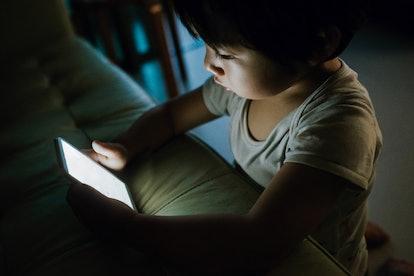 young boy watching screen in the dark