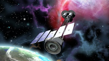 NASA IXPE satellite in orbit around Earth, with colorful effects that imply X-rays