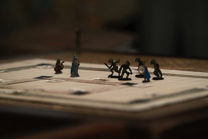 A production still of Stranger Things showing a dungeons & dragons game board with playing pieces. Here's how to play D&D online on zoom.