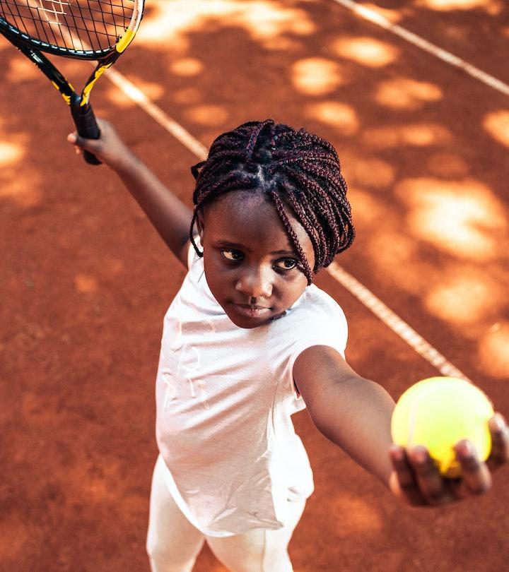 Child serving tennis ball