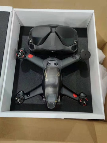 A possible DJI FPV drone in a white box. The body of the drone is mostly black and gray with a duller gray top.