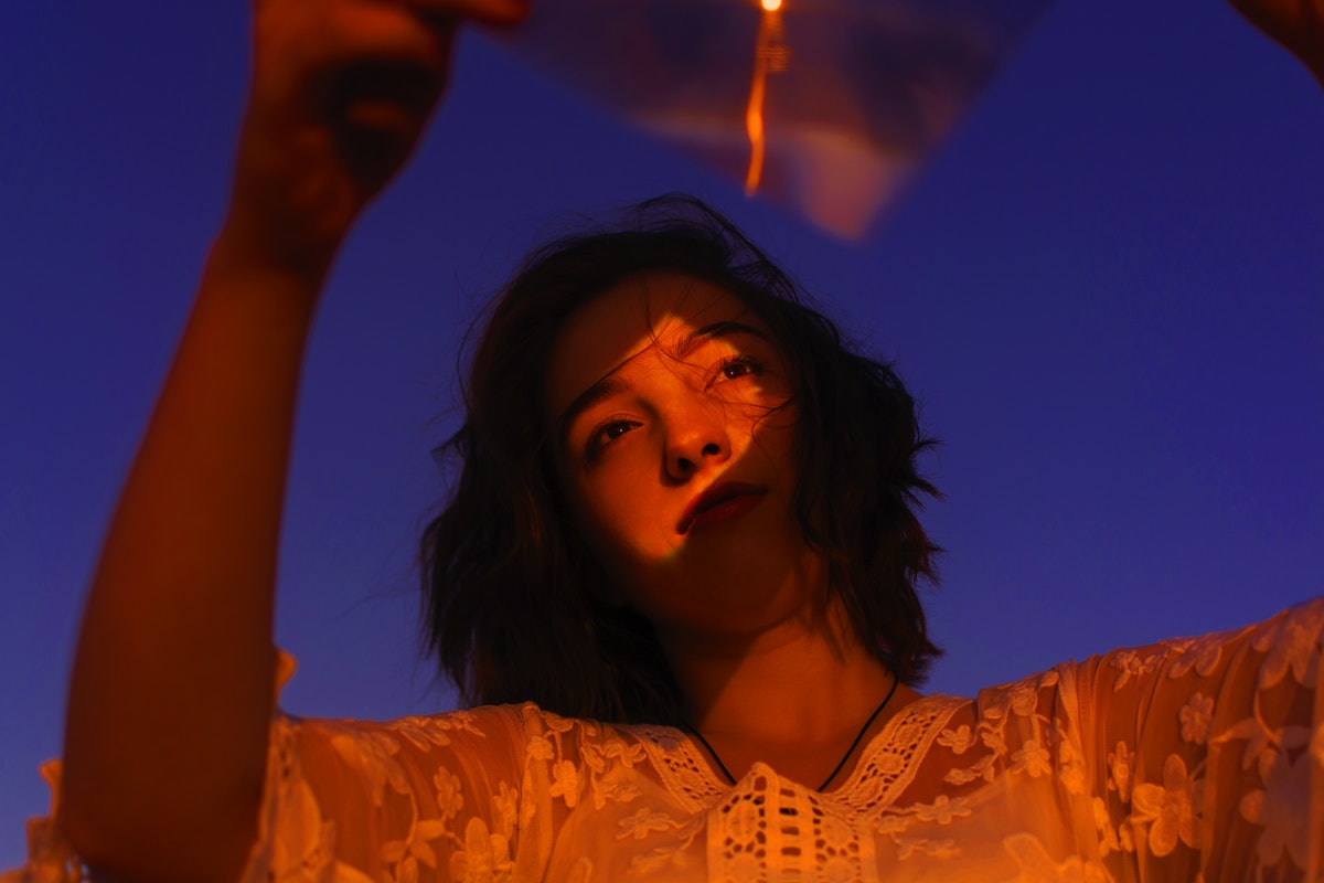 Young Woman Looking Away While Holding Plastic With Reflection On Face Against Sky