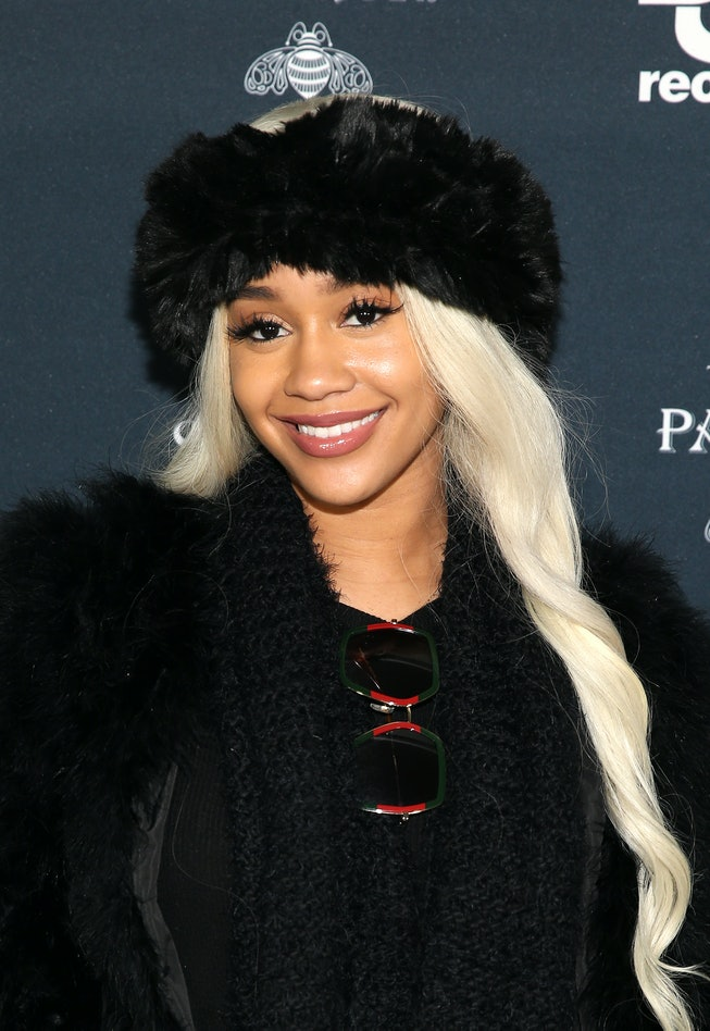 Rapper Saweetie with long platinum blonde hair and winter hat.