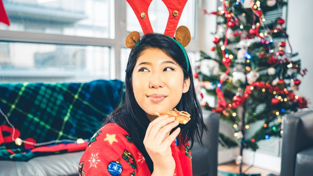 Young woman eating Christmas pizza