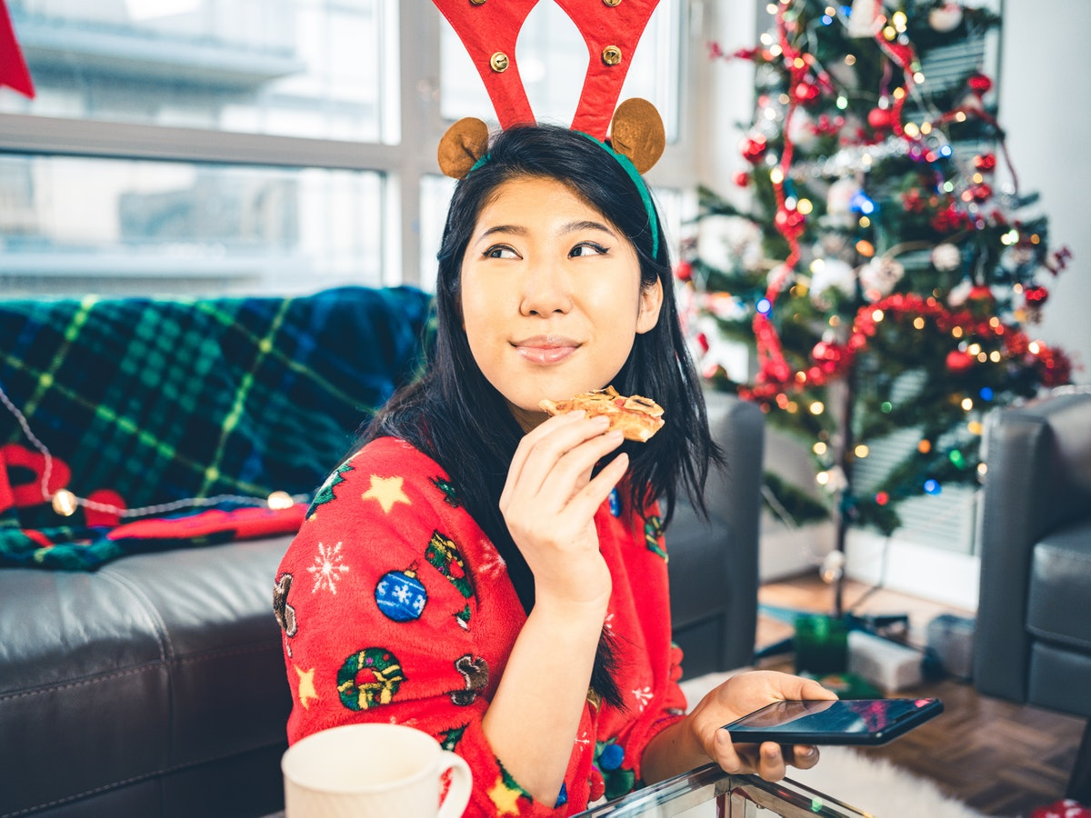 Young woman eating Christmas pizza