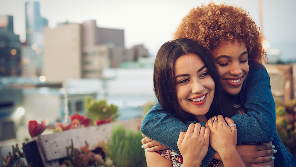 Friends hugging on urban rooftop