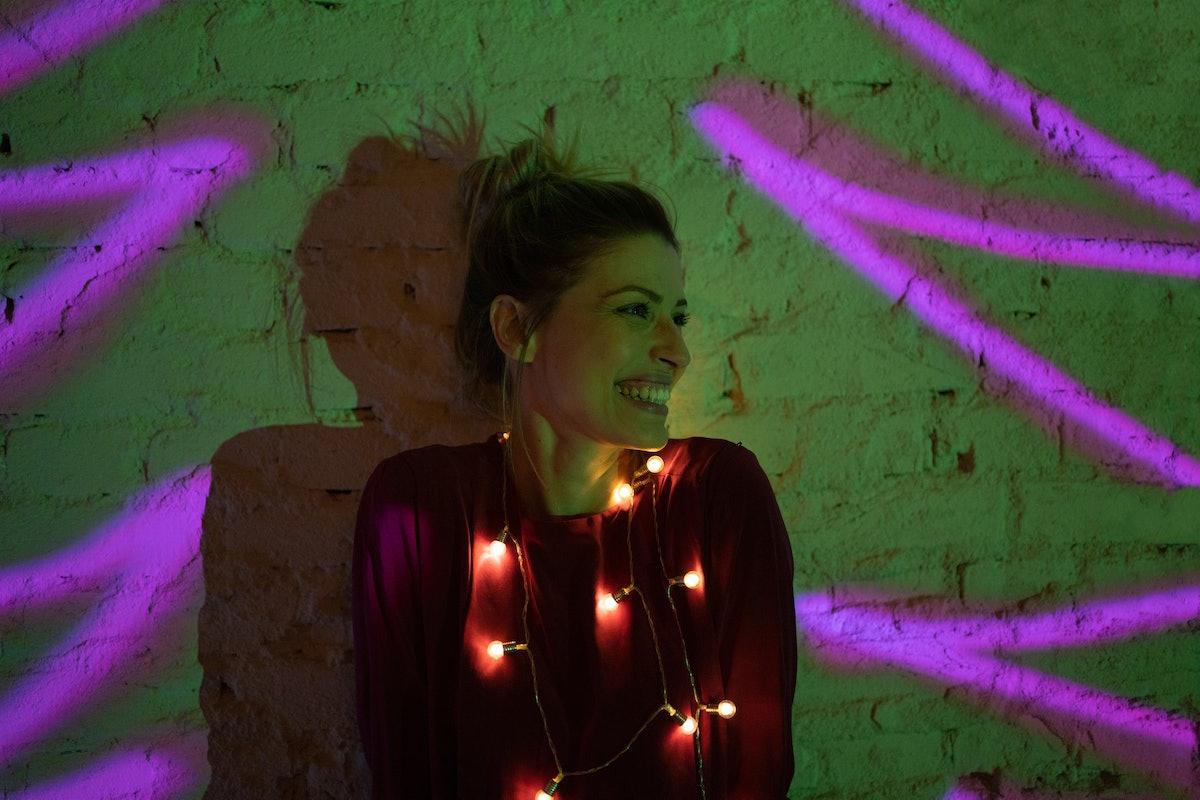 Young woman wearing Christmas lights
