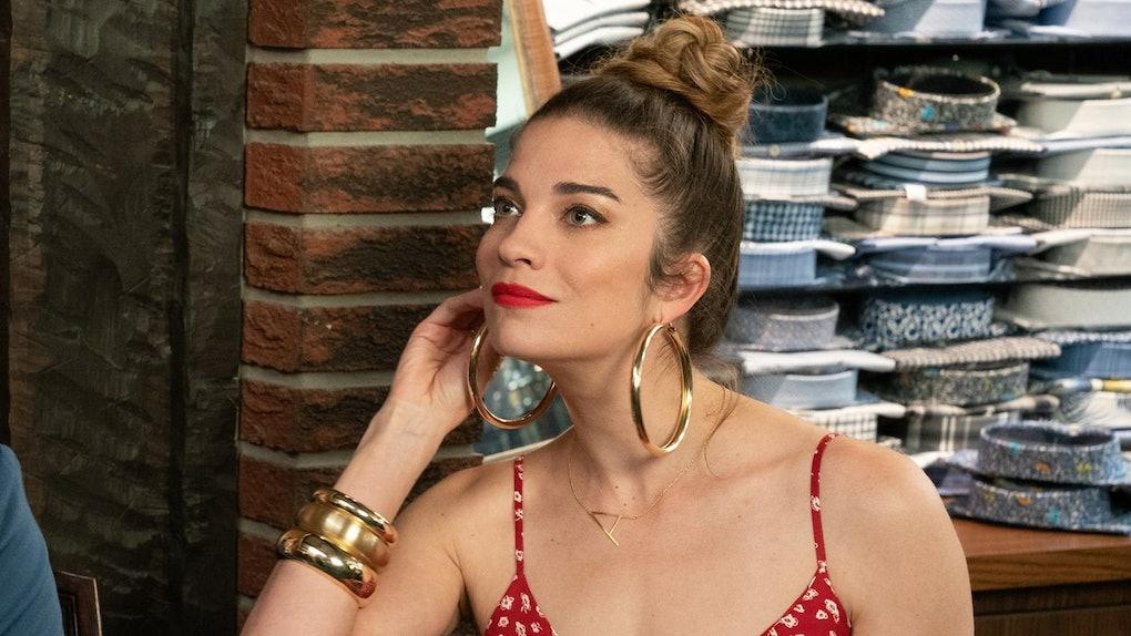 Alexis (Annie Murphy) wears gold hoods and a red sundress in 'Schitt's Creek.'