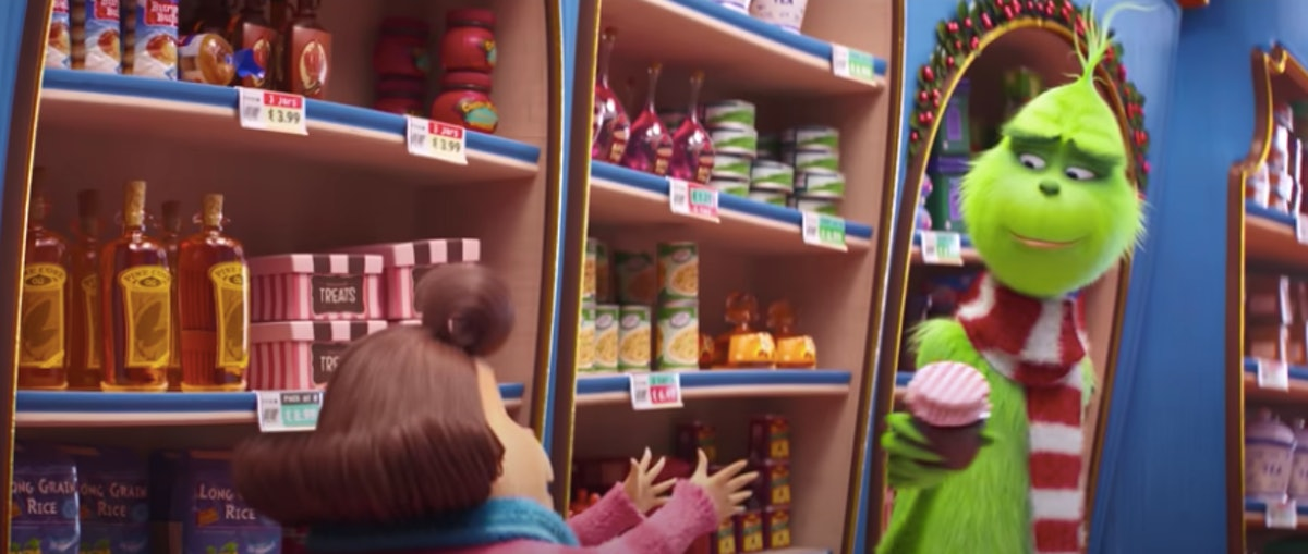 The Grinch holds a jar of jam and smiles in a store in Whoville.