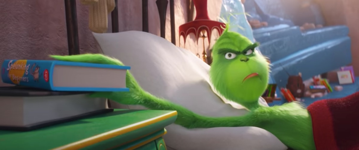 The Grinch frowns while grabbing a book in bed.