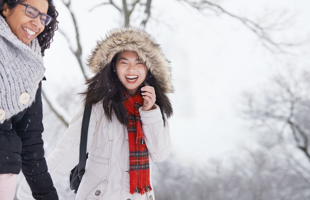 Two young woman walking in winter snow