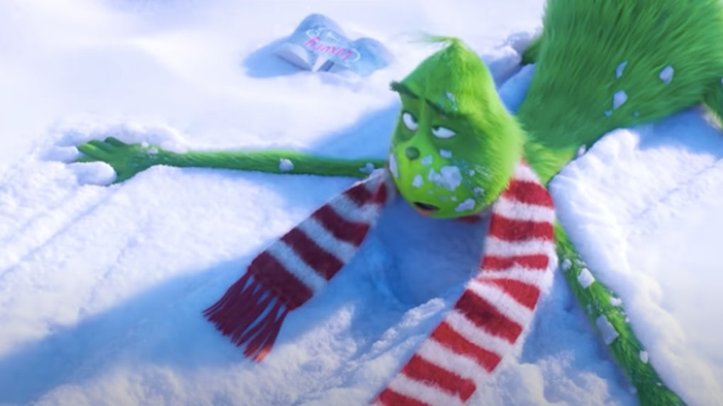 The Grinch lays on his stomach in the snow after getting knocked over by an inflatable snowman.