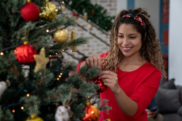 Latin woman looking happy decorating the Christmas tree