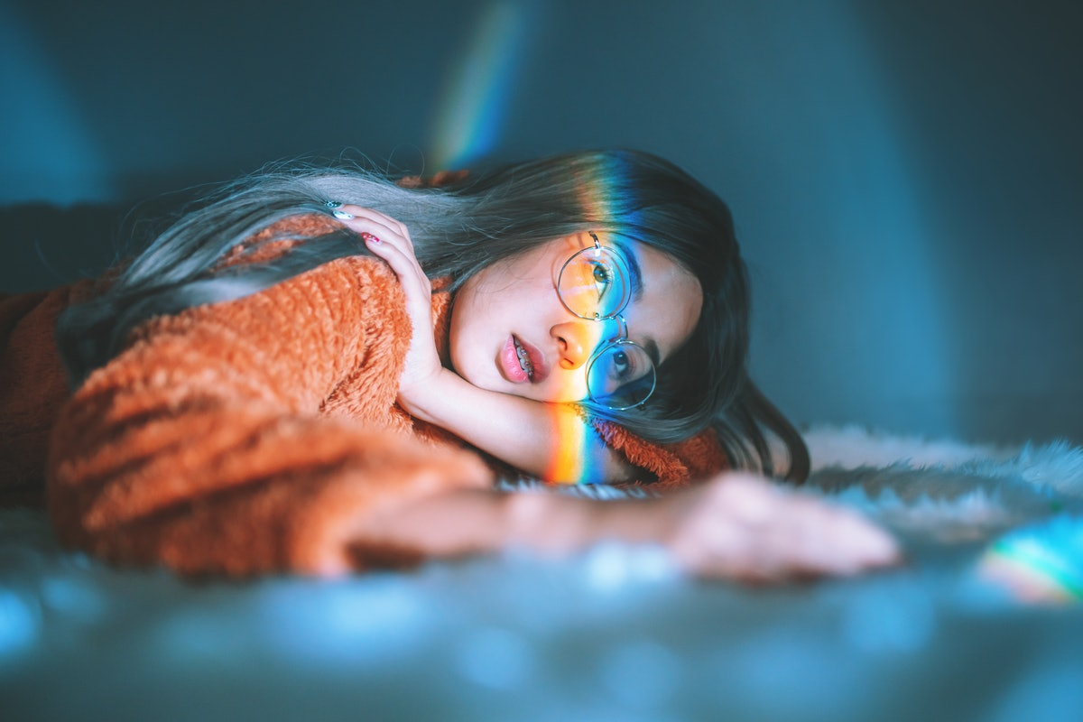 Woman Lying Down On Bed With Rainbow On Face