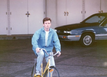 A young Rick Astley can be seen on a bicycle in Vegas. There is a car parked behind him.