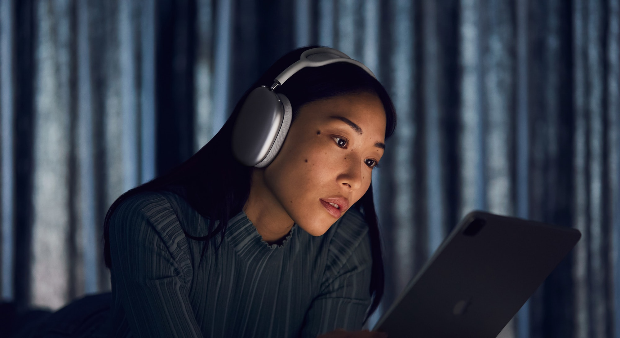 A woman wears Apple's new AirPods Max while on her iPad at night.