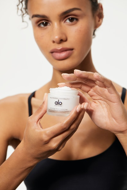 Model holding the facial moisturizer from Alo Yoga's new beauty line.