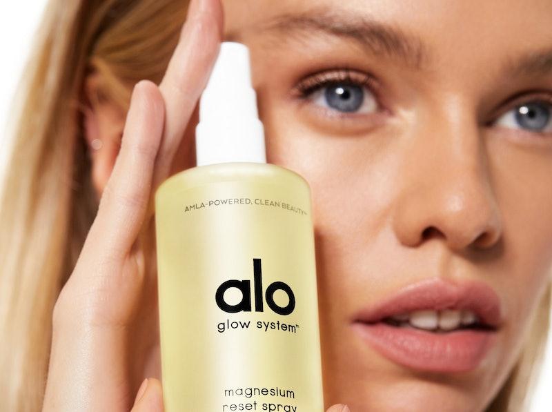 Model holding the facial spray from Alo Yoga's new beauty line.