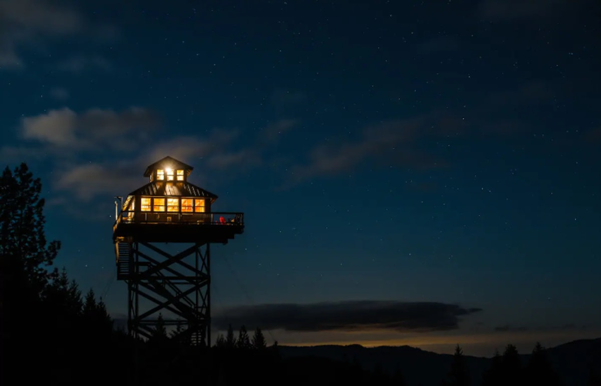 A tower listed on Airbnb sits above the trees in Oregon, all lit up in the evening.