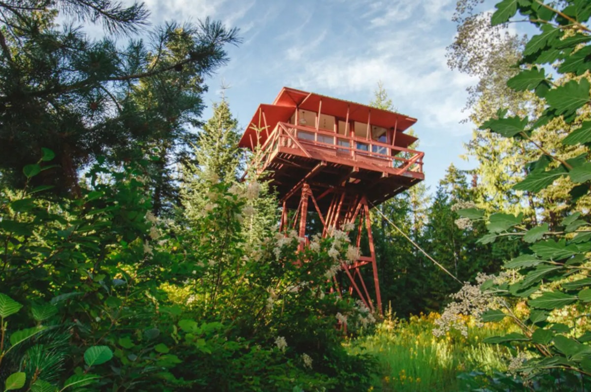 The Crustal Springs Lookout tower on Airbnb is red and sits above the trees in Idaho.
