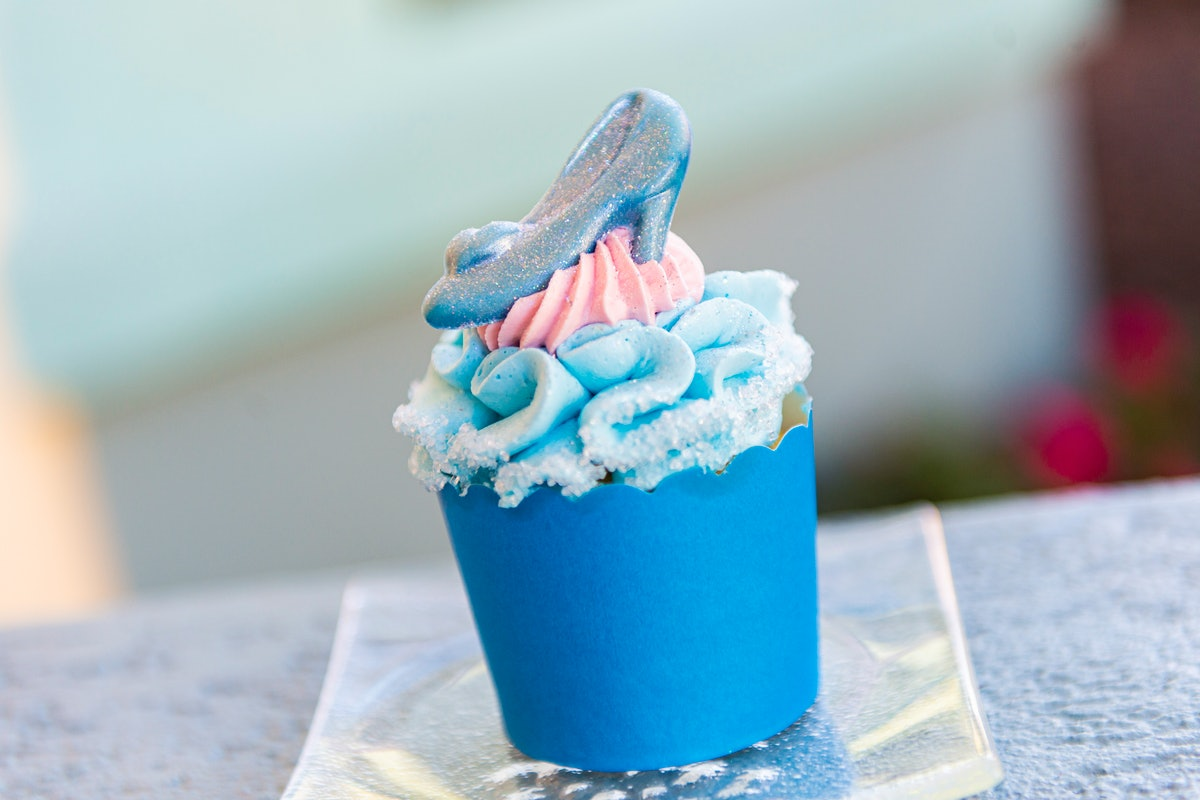 A blue and pink 'Cinderella'-inspired cupcake sits on the table with a chocolate glass slipper on top.