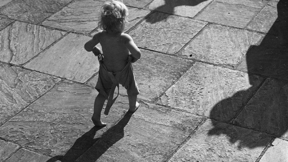 1980s toddler walks toward sun