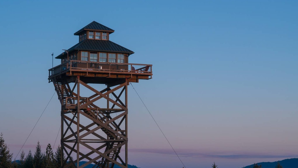 A tower listed on Airbnb overlooks the forest in Oregon during the sunset.