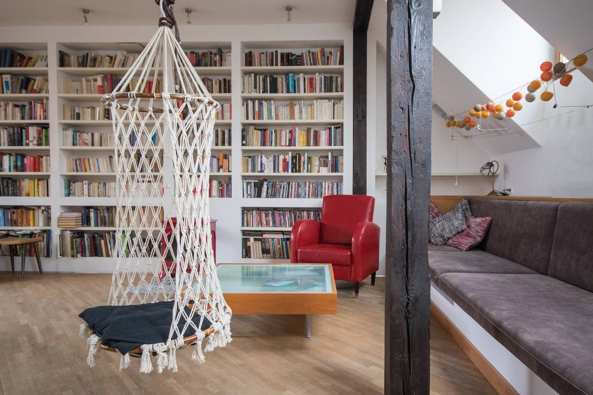 A swing hangs in the middle of a living room on Airbnb with bookshelf walls, just like the library i...