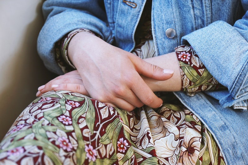 A woman sits with her hands folded on a printed skirt. Eating disorder statistics show that many myths about the disease are more harmful than you'd think