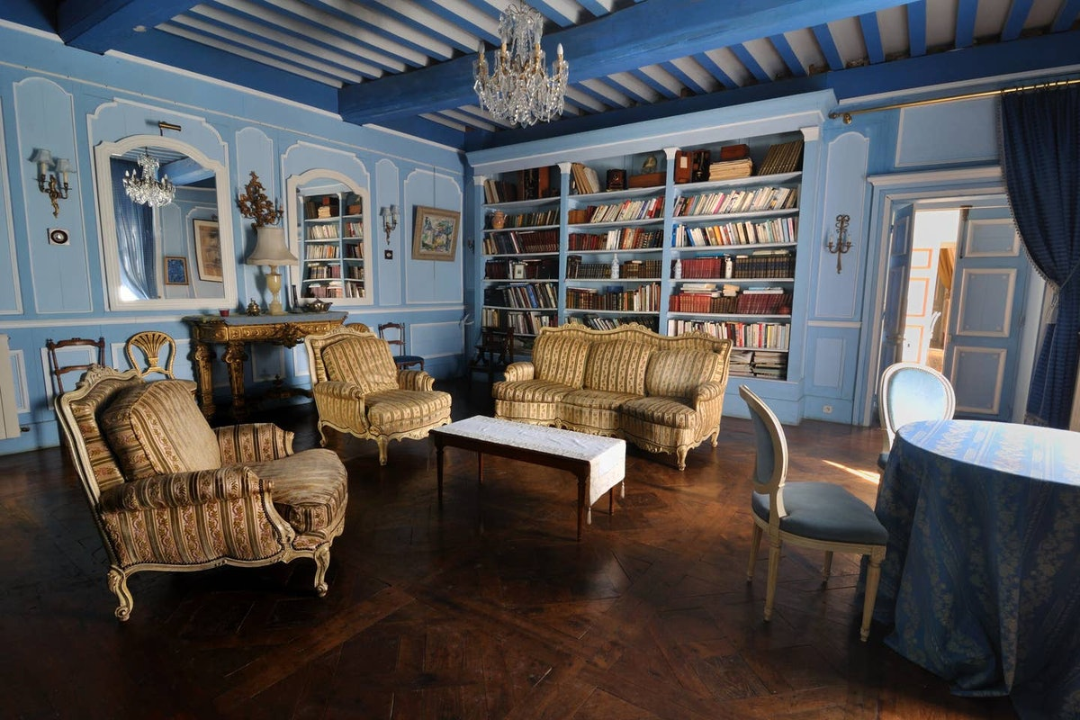 An elegant blue room in an Airbnb castle has books on the shelves, just like the library in 'Beauty ...