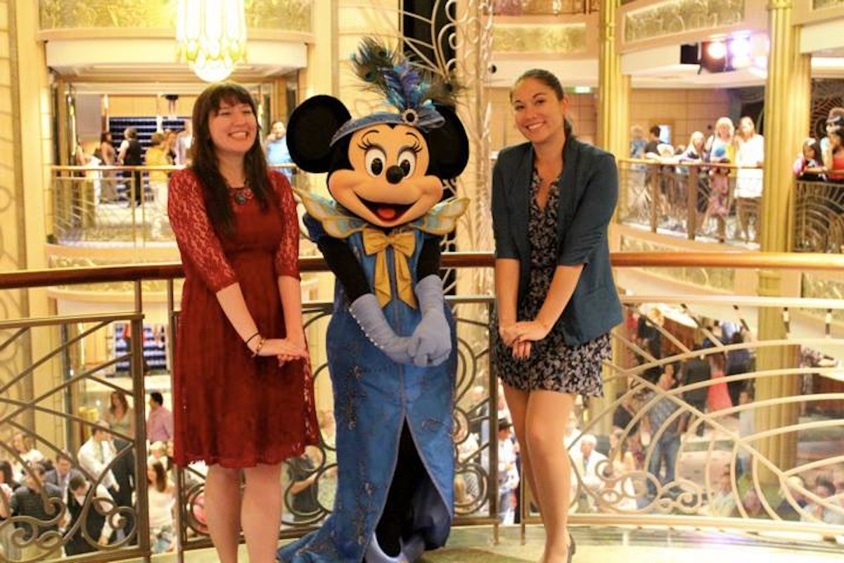 Two friends pose with Minnie Mouse in formal attire on a Disney Cruise.