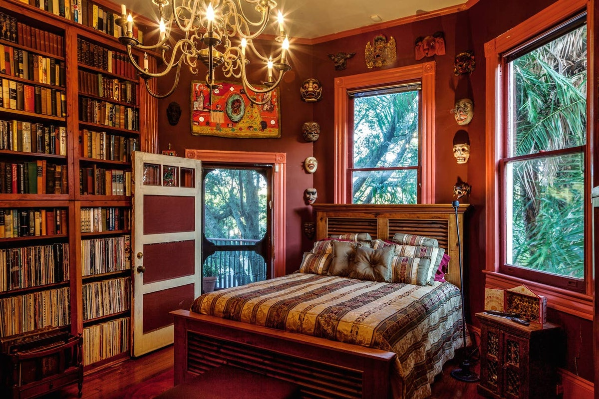 A bedroom in a New Orleans Airbnb has books on the shelves, just like the library from 'Beauty and t...
