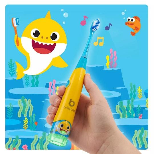 Brite Brush baby shark toothbrush in front of cartoon ocean background