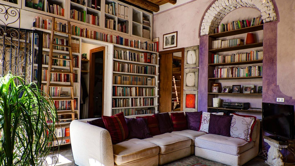 Books fill the bookshelves on the walls of this bright living room that's listed on Airbnb.