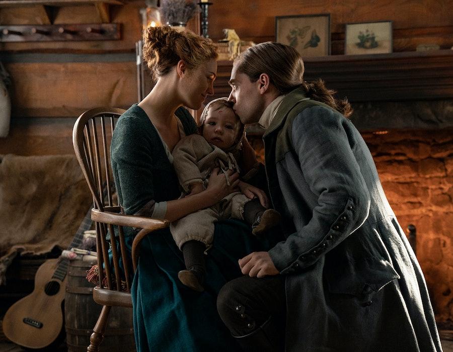 "Sophie Skelton as Brianna ""Bree"" Randall, Richard Rankin as Roger Wakefield, and their son Jeremiah in Outlander Season 5"
