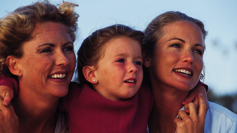 Three generations of females hug in an archival photo from the 1980s