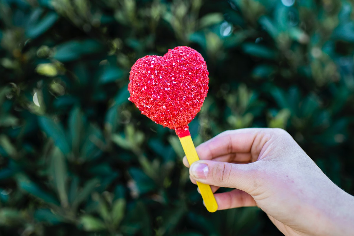 A woman holds up the Queen of Hearts inspired heart-shaped cake pop from the Disney Villains After H...