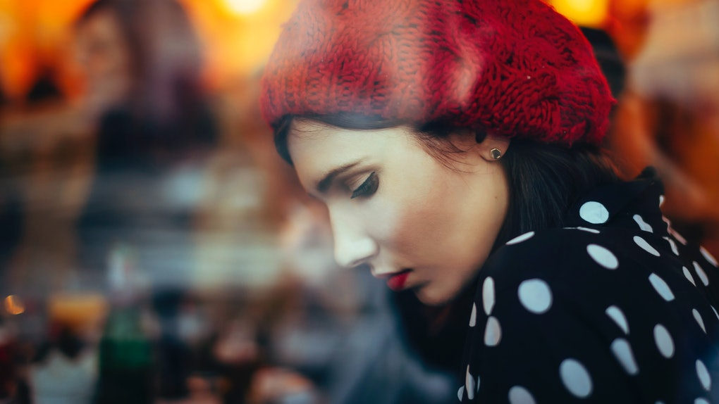 Young woman with red hat in window