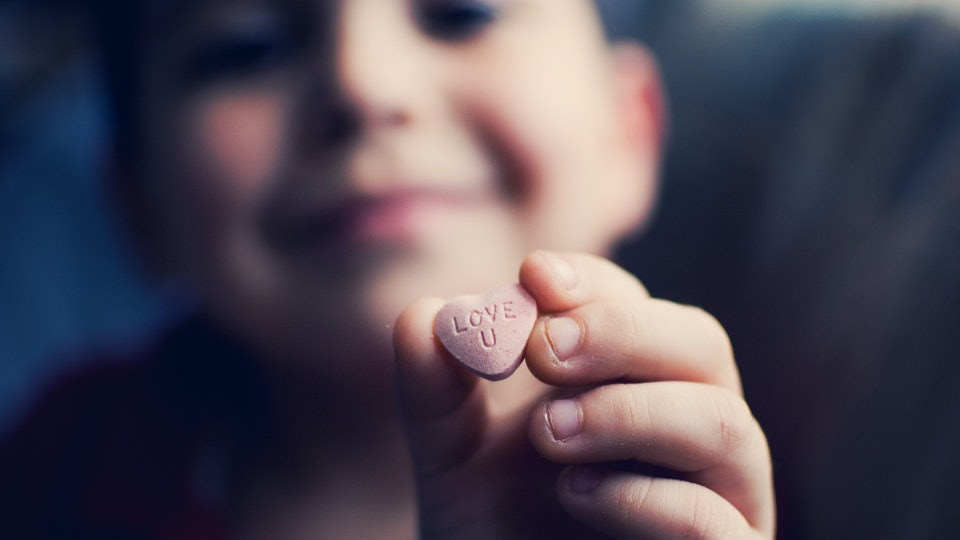 A boy holds up a candy heart