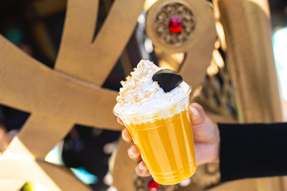 A woman holds up a yellow slush drink inspired by Jafar from 'Aladdin' for the Disney Villains After...