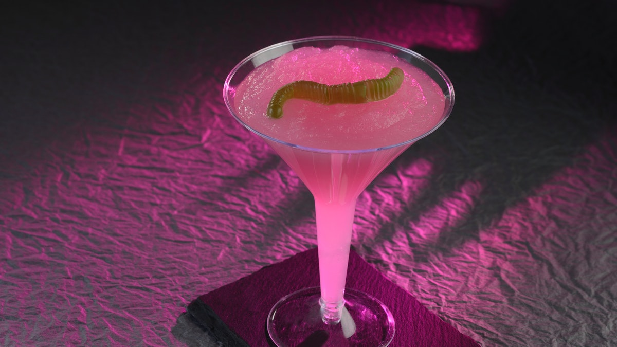 A pink mocktail inspired by Hades from 'Hercules' sits on a table at Disney for the Disney Villains ...