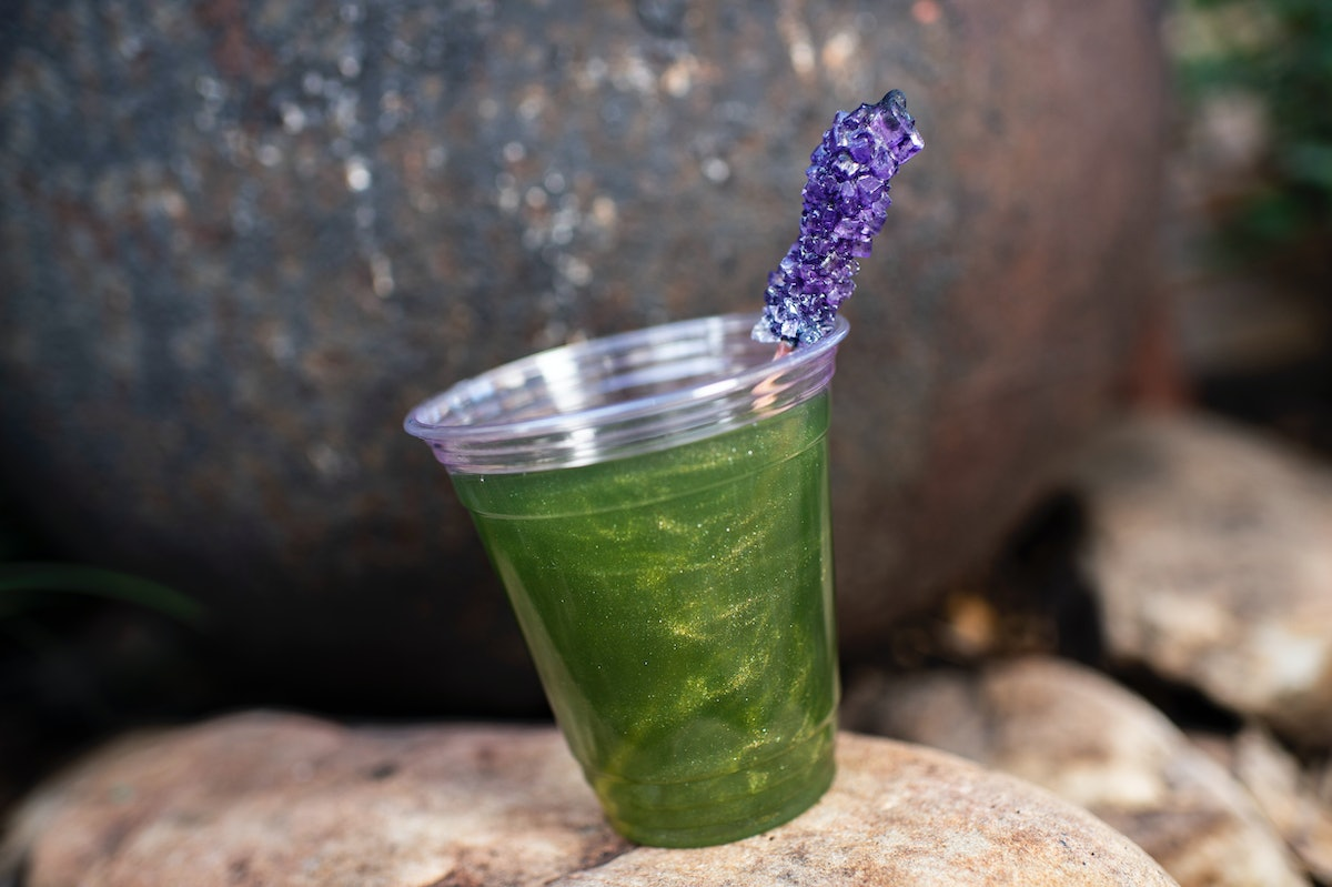 A green lemonade inspired by Dr. Facilier from 'The Princess and the Frog' sits on a rock at the Dis...