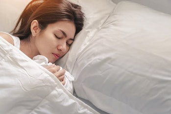 Young asian woman sleeping alone on white pillow on bed in bedroom on morning time, copy space.