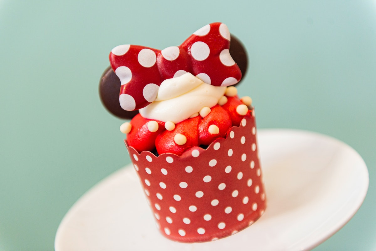 A Minnie Mouse cupcake with chocolate ears and red and white icing sits on the table for Valentine's...