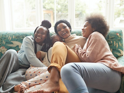 A mother plays with her three teenaged daughters on the couch