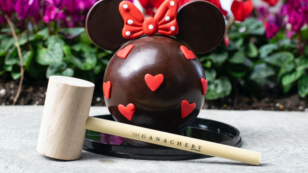 A Minnie Mouse-shaped chocolate piñata sits on the table with a wooden mallet for Valentine's Day at Disney.